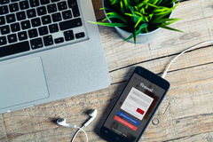 马拉加,西班牙- 2015年10月29日:在一个手机屏幕的Pinterest app,接近一台计算机,在一张木书桌 免版税库存照片
