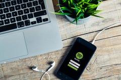 马拉加,西班牙- 2015年10月29日:在一个手机的Spotify app,接近一台计算机,在一张木书桌 免版税库存照片