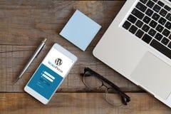 马拉加,西班牙- 2015年12月15日:Wordpress一个手机屏幕的注册网站app,在一个木工作场所 WordPress是a 免版税库存图片