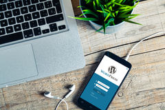 马拉加,西班牙- 2015年10月29日:Wordpress一个手机屏幕的注册网站app,在一个木工作场所 WordPress是f 免版税图库摄影