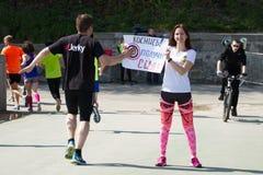 马拉松在Kyiv,乌克兰 站立与横幅的俏丽的女孩 免版税库存图片