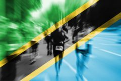 马拉松运动员与混和坦桑尼亚旗子的行动迷离 免版税图库摄影