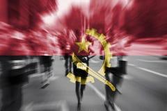 马拉松运动员与混和安哥拉旗子的行动迷离 库存照片