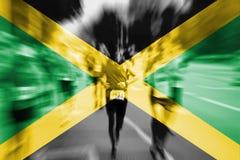 马拉松运动员与混和牙买加旗子的行动迷离 库存照片