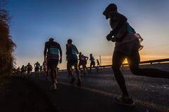 马拉松运动员特写镜头现出轮廓日出 免版税库存照片
