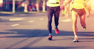马拉松运行在城市道路的运动员腿 免版税库存照片