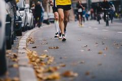 马拉松连续种族,在秋天路的人脚 赛跑者参加uMarathon连续比赛,在秋天路的人脚 赛跑者奔跑urb 库存图片