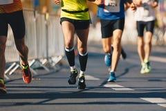 马拉松连续种族,在秋天路的人脚 赛跑者在街市跑都市马拉松 免版税库存照片