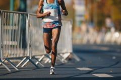马拉松连续种族,在秋天路的非洲妇女脚 跑都市马拉松的非洲赛跑者在城市 库存图片