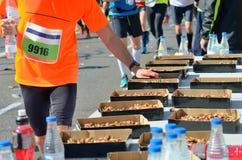 马拉松连续公路赛,赛跑者递采取食物,并且在茶点的饮料指向,炫耀,健身和健康生活方式 免版税库存照片