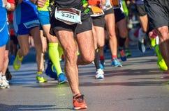 马拉松连续种族,在路的人脚 免版税库存图片