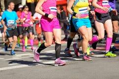 马拉松连续种族,妇女在路的赛跑者脚 免版税库存照片