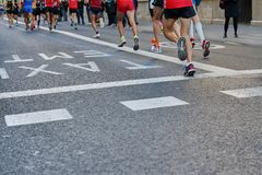 马拉松长跑,跑在城市道路的人的脚 免版税库存图片