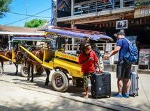 马推车在Gili Meno海岛,印度尼西亚搭载在街道上的游人 免版税库存照片