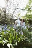 马服装的女孩有母亲的在花园里 免版税库存照片