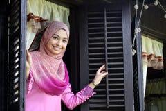 马来的回教妇女打开一个传统窗口 免版税库存照片