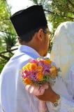 马来的夫妇举行婚礼花花束 免版税库存图片