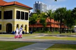 马来的女学生在部落迷人的庭院,新加坡里走 免版税库存照片