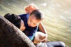 马来西亚母亲抱着她的接近她的胸口的婴孩 免版税图库摄影