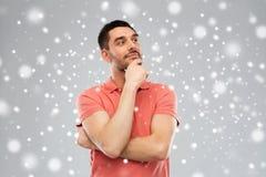 马球T恤杉的人认为在雪背景的 免版税库存照片