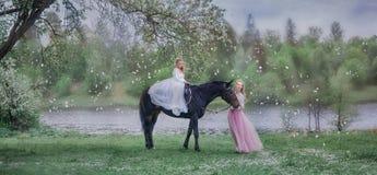 黑马的女孩在开花庭院里 免版税库存图片