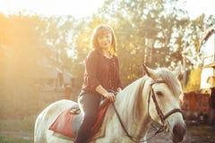马的妇女在日落 免版税库存照片