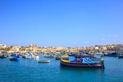 马耳他,充分Marsaxlokk历史的口岸小船 蓝天和村庄背景 库存图片