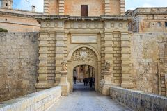 马耳他,姆迪纳入口门 游人横渡人行桥参观历史的被加强的镇 库存照片