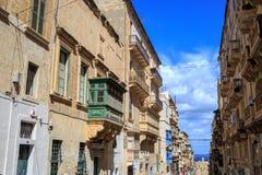 马耳他,瓦莱塔,与五颜六色的木窗口的传统砂岩大厦在阳台 与云彩和海backgroun的蓝天 库存照片