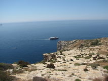 马耳他-横渡海岛的小船在蓝色洞穴附近 库存照片