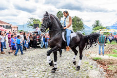 马背女牛仔乘驾在村庄,危地马拉 免版税图库摄影