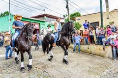 马背牛仔&女牛仔乘驾在村庄,危地马拉 库存照片