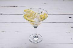 马蒂尼鸡尾酒用在一块玻璃的一个柠檬在一张白色桌上 免版税库存照片