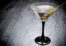 马蒂尼鸡尾酒用在一张黑桌上的橄榄 文本的空位 免版税图库摄影