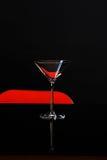 马蒂尼鸡尾酒的一块被隔绝的玻璃在黑暗和红色背景 鸡尾酒 免版税库存图片