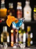 马蒂尼鸡尾酒饮料在与冰块的玻璃桌上服务 库存照片