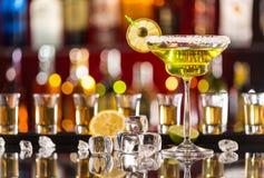 马蒂尼鸡尾酒饮料在与冰块的玻璃桌上服务 图库摄影