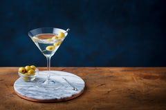 马蒂尼鸡尾酒鸡尾酒用在大理石切板的绿橄榄 复制空间 免版税图库摄影