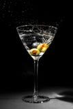 马蒂尼鸡尾酒玻璃用两个飞溅的橄榄 库存图片