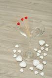 马蒂尼鸡尾酒玻璃用用心脏装饰的三根棍子 库存图片
