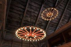 马车车轮从一个谷仓的天花板有光的垂悬了一次传统古板的婚姻的庆祝的 库存照片