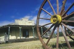 马车车轮和老大厦在南TX鬼城 免版税库存图片