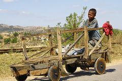 马达加斯加男孩运载一个传统caresa支架 免版税图库摄影
