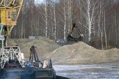 马达平地机排列土路 在移动与桶的轮子的一台推土机 轮子拖拉机移动与bucke的石渣 免版税库存照片