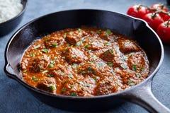 马都拉斯辣黄油的牛肉减慢厨师羊羔食物用在生铁平底锅的蕃茄 图库摄影