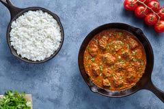 马都拉斯辣黄油的牛肉减慢厨师羊羔食物用米和蕃茄在生铁平底锅 免版税库存图片