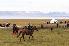 马骑术在歌曲kul湖在吉尔吉斯斯坦 库存照片