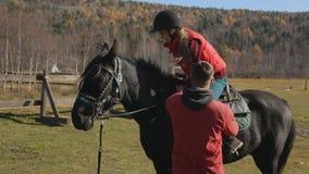 马骑术教练员帮助女性初学者第一次登上 股票录像