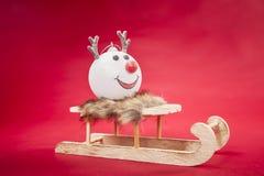 驯鹿中看不中用的物品坐一个雪橇,在红色背景 图库摄影