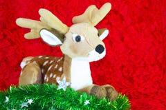 驯鹿和绿色树在红色背景 圣诞节快活的新年度 免版税库存照片